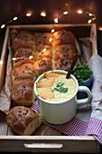 Mais-Curry-Suppe serviert in Tasse mit Tortillachips und Hefegebäck