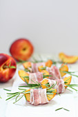 Nectarine slices wrapped in ham with rosemary