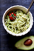 Spaghetti with avocado cream garnished with a cocktail tomato (close up)