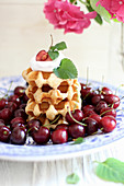 A stack of Belgian waffles with cream and fresh cherries