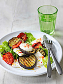 Char grilled aubergine salad with roast tomatoes lettuce and feta cheese