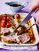 Carving easter rack of lamb with roast tomatoes and gravy