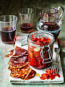 Spanish roast peppers in oil and garlic in jar with chorizo iberico ham and sangria