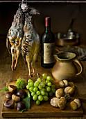 Herbstliches Stillleben mit Rebhühnern, Kastanien, Trauben und Steinpilzen