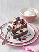 Slice of black forest gateau with cherries and bowl of cream