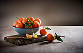 Mandarins in a bowl on a wooden board with a paring knife