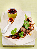 Sausage flatbread wrap with tomato relish and coriander