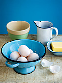 White eggs in blue culander with butter and meauring jug