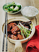 Slow cooked chinese pork with soring onions pak choi and rice