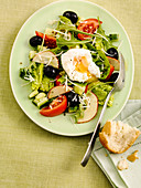 Poached egg salad with black olives, apple and french bread