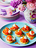 Easter lunch of smoked salmon and salmon caviar on blinis o an Easter table setting