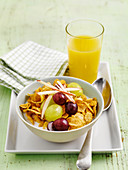 Cornflakes, grapes and shredded apple with orange juice