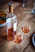 Provenzalischer Rosewein in Flasche und Gläsern auf Holztisch