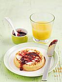 English crumpet with cherry jam served with orange juice