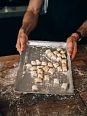 Hände halten Backblech mit selbst gemachten Gnocchi