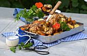 Roast chicken with root vegetables on a table outside