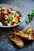 Salsa with feta cheese, pomegranate seeds and grilled bread