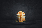 A cheesecake cupcake with apple sauce and caramel sauce