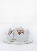 A cake inside a fabric napkin folded as a flower