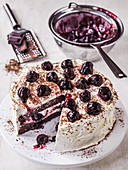 Black Forest Gateau with glazed cherries and a slice cut out along with grated chocolate
