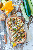 Pizza with zucchini, zucchini flowers and pine nuts
