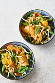 Oriental bowls with papaya salad, nuts and a honey and sesame seed dressing
