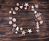 Lebkuchenplätzchen, Nüsse, Zimtstangen und Weihnachtsdekoration kreisförmig angerichtet auf Holzuntergrund