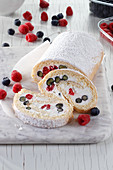 Sponge roll with cream and raspberries and blueberries