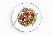 Tasty vegetable salad with fig served with fork