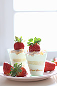 A layered dessert with strawberries and flaked almonds in glasses