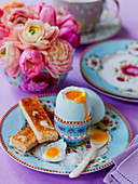 Easter breakfast boiled egg and buttered slices of toast soldiers with spring flowers