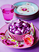 Easter eggs in bowl with tulip flower stack of floral plates and pink glass
