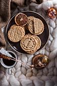 Selbst gebackene Kekse in einer Metalldose, Kaffee mit Kandisstangen und Weihnachtsdekoration