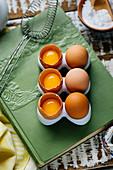 Keramik Eierbehälter mit ganzen und aufgebrochenen Eiern auf grünem Buch