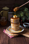 Stack of tasty pancakes served with butter and honey