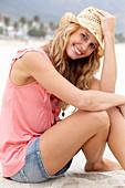 Junge blonde Frau im rosa Top, kurzem Jeansrock und beigem Hut am Strand