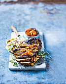 Gegrillte Lammkeule, mariniert mit Buttermilch und Curry, dazu Chutney aus getrockneten Aprikosen