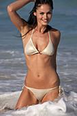 Junge brünette Frau im silbernen Bikini am Strand