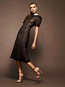 Junge brünette Frau im schwarzen Abendkleid