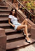 Junge dunkelhaarige Frau in sommerlichen Outfit sitzt auf Treppe