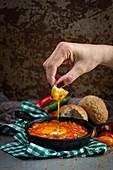 Spiegeleier mit Tomaten und Paprika in der Pfanne serviert mit Brot zum Dippen (Spanien)