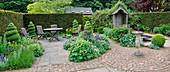 Sitzplatz auf Terrasse zwischen Beeten, gepflastertes Rondell mit Sonnenuhr