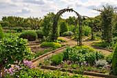 Sternförmig angelegter Nutzgarten mit Rosenbögen, Wegen und eingefaßten Beeten