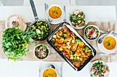 Gedeckter Tisch mit Kürbissuppe, Brathähnchen und Salat
