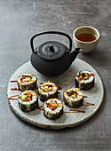 California Rolls mit Pulpo, Avocado und schwarzem Sesam serviert mit Tee