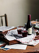A bottle of red wine and red wine glasses on a wooden tray on a wooden table