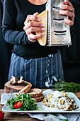 Frau reibt Parmesan über Rührei mit Pilzen