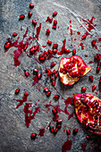 Pieces of pomegranate and pomegranate seeds on a grey surface