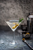 Martini cocktail with rosemary and olives