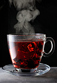 Steaming hibiscus tea in a glass cup
